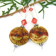 The rustic spiral shell beads used in this pair of handmade, one of a kind earrings are reminiscent of ancient fossils that have been buried underground for millions of years. The unique SPIRALS OF TIME dangle earrings feature Czech glass spiral shell discs and sparkling padparadscha Swarovski crystals.