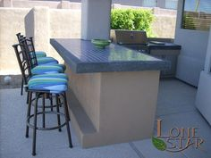 This outdoor kitchen barbecue area has a bar with black cantera trim with blue tile in Scottsdale, AZ. - www.lonestaraz.com