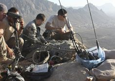 Soldiers watching a valley from a mountain top utilize networked AN/PRC-117G wideband radios to communicate tactical information to units below.