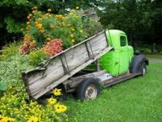 Old truck with wood bed, filled with flowers....love it