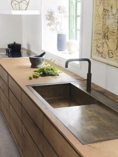 Remodelista | Rene Redzepi's kitchen | continuous oak countertop and cupboards with aged brass sink