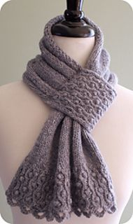 "A lush and elegant scarf showcasing a simple twisted stitch cable and bobble design. The sides are finished with an i-cord that is knit while you work the scarf, the bottom with a simple looped edging. Knitted pleats gather the scarf from 12"" wide to 4"" wide, where a small cabled panel is folded to create a loop through which you pull your scarf end. Knit in Rowan Lima, this scarf is light, yet lofty and oh so cozy."