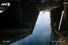 A picture taken on January 21, 2017 shows a reflected image of Iraqis standing next to a bridge on the Khusar river which was destroyed by Islamic State (IS) group fighters in Mosul's al-Sukkar...