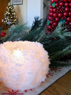 snowball candle looks beautiful w/ greens around it
