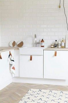 White and light kitchen with a little wood. #handles #leather