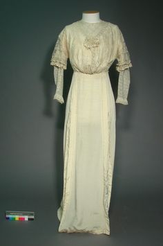 "Edwardian wedding gown, ca. 1914. Silk grosgrain & lace, lined w/cotton & trimmed w/pearls. Gown is ""an intriguing example of the transition from the tightly corseted construction of the Edwardian era to a softer, more free-flowing style of dress. It is sewn with all of the internal detail for extensive boning but without the actual stiffening itself."" Toitū Otago Settlers Museum, Dunedin, NZ, via eHive"