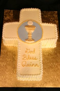 First Communion Cross with Chalice and Host - This cake is a yellow cake filled and iced in vanilla buttercream, then cut into the shape of the cross.  All detail is buttercream except the blue disc, gold chalice and off-white host which were all colored white chocolate.  This cake and the pink birthday cake were for the same event, but the family wanted to celebrate a birthday while everyone could be together for the First Communion.  I did the same stripes on both cakes to help tie them…
