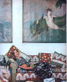 Interior designer Justine Cushing reclining on her mother's Southampton house couch, above which are her grandfather Howard G. Cushing's otherworldly paintings. The couch and cushions are upholstered in Indian prints. It can all be a chaotic, clashing mishmash but everything goes well beautifully — even Ms. Cushing's striped top and floral skirt blend perfectly. A hard skill to master, as anyone who has tried to mix patterns today can attest to. Photo by Horst P. Horst.  Vogue, November…