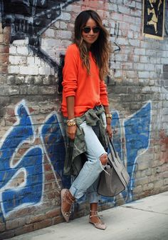 Julie Sarinana of Sincerely Jules contrasts her light wash distressed jeans with a bright orange sweater, camo, and neutral accessories. // #Denim