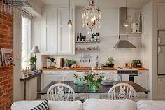 Pequeños espacios integrados. La cocina tiene sólo sitio para lo básico e indispensable. Aprovecharon la ventana para hacer un pequeño escritorio sobre el radiador