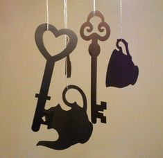 Alice in wonderland hanging decorations. Keys, tea cups, tea pot shaped silhouette for a themed wedding/ party. By Rae Henry Designs.