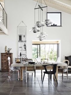 Amazing dining room with different unique chairs and a beautiful pendant from Louis Poulsen.