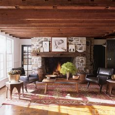 In the great room of artist Deborah Buck's 19th-century farmhouse in New York's Hudson Valley, the cocktail table in front of the fireplace is by George Naka shima Studio, the chairs are by Gio Ponti, and the Persian rug is antique.   Tour the entire home.   - ELLEDecor.com