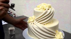Wedding cake made with butter cream roses covered in fondant icing designed with sugar drapes and butter cream icing the cake is vanilla cake with bavarian c...