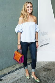 Olivia Palermo wears a blue off-the-shoulder blouse, cuffed skinny jeans, printed ballet flats, and a colorblocked top handle bag