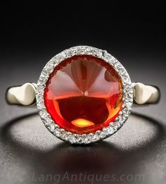 Orange Fire Opal and Diamond Ring, A vibrant orange-saffron colored Mexican Fire Opal, with a sleek and distinctive sugar-loaf-cut, beams from within a glittering halo of bright rose-cut diamonds in this Victorian Style ring crafted in silver over 14K yellow gold supported by a lattice under gallery.