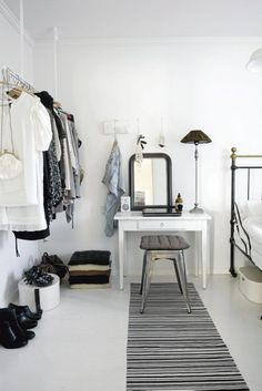 clothes rack on left side, dressing table on back wall