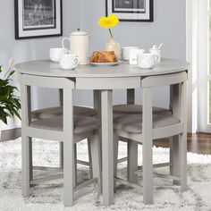 Perfect for smaller spaces the 5-piece Tobey Compact Dining Set by Simple Living offers a stylish mid century solution. Featuring an expertly designed round table with four angled dining chairs that w