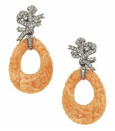 A pair of earrings set as carved coral, corallium rubrum, open pear-shaped drops to marquise and brilliant-cut diamond floral surmounts, post and clip fittings, 5.5cm long [I'm not into the cherub thing but the carving is pretty amazing.]