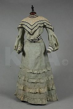 Lot 1197: A pale green figured gauze day dress, circa 1905,  A pale green figured gauze day dress, circa 1905, with chemical lace yoke and collar, pouter-pidgeon silhouette bodice, trimmed with velvet ribbon, matching skirt; together with the remains of an altered 1880s evening gown, cotton bloomers and others