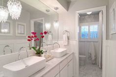 Such pretty lighting accents and the pop of color through the flowers is beautiful. I especially love the faucets, sinks and water closet. Impeccable!