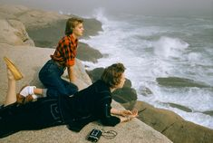 Two women gaze at heavy surf while lying on boulders on the coast of Nova Scotia, December 1961.Photograph by Volkmar Wentzel, National Geog...