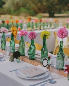 Mismatched vintage dinnerware, antique green bottles filled with dahlias, wooden planks, and baby artichokes adorned the long tables, which were covered with off-white linens and set with wood chairs.