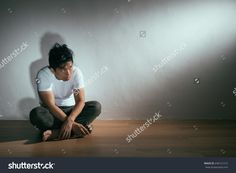 young autism patient man sitting on wooden floor looking at empty dreaming fantasy feeling afraid with white background in dark display autistic intellectual disability concept.