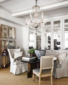 A simple sisal carpet is a counterpoint to a sparkling chandelier in a dining room in Sydney. | Photo: Anson Smart, Design: Thomas Hamel