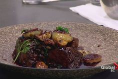 Quang Dang, executive chef of Araxi Restaurant + Oyster Bar,prepares braised Brant Lake Farm wagyu short ribs, caramelized cippolini onions, mushrooms and parsley