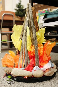 CLASSROOM CAMPFIRE ~~~ Of course we had to have a fire! I built this with rocks and sticks from our yard, a black fabric covered bucket lid, and tissue paper. Andrew's construction glue keeps it all attached. Inside the tissue paper is a string of orange twinkle lights. We plug it in and enjoy our glowing fire on special occasions, or when we are gathered around to hear one another's writing.