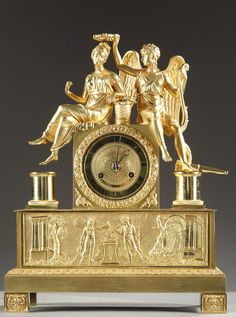 A gilt and chiseled bronze mantel clock with Cupid holding a bow in one hand and a crown in the other over the head of Psyche. She sits on the...