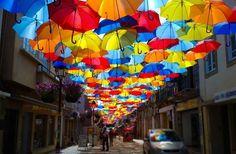 """Em Agueda, cidade pertencente ao distrito de Aveiro, Portugal, seus moradores enfeitam esporadicamente a cidade assim, com uma rua repleta de guarda chuvas como se fosse uma espécie de telhado. A rua despertou a atenção do mundo inteiro, não somente pela criatividade, mas também pelo contraste das cores em contato com o sol. A instalação faz parte de um festival de arte e cultura chamado """"AgitAgueda"""" promovido pela prefeitura da cidade."""