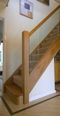 Steel and wood stairs with a glass handrail lead up to the second floor of this modern house.