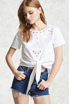 A woven top featuring a round neckline, button-down back, short sleeves, a self-tie front hem, and a front ornate embroidery with laser-cutouts.