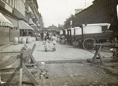 See how it's changed: In this circa 1890 photo, a pair of girls walk east along 42nd Street. Acker, Merrall and Condit wine shop delivery wagons are on the right and the C.C. Shayne Furrier sign can be seen on the roof overhead.
