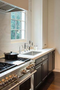 Black lower kitchen cabinets. black and white modern kitchen. love the all the way to the ceiling marble backsplash.