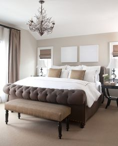 Beautiful bedroom with clay beige walls paint color, chocolate brown tufted sleigh Eloise Bed from Brownstone Upholstery, ebony stained nightstands, taupe velvet curtains widow panels, Pottery Barn Camilla 6-Arm Chandelier and brown bench
