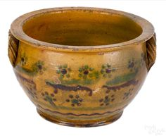 """Pook & Pook. The Collection of J. Jefferson and Anne Weiler Miller. April 25th 2015 Lot 1129. Southeastern Pennsylvania redware bowl, early 19th c., with green and brown slip decoration and rope twist handles, 5 1/4"""" h., 8 1/4"""" dia. Significant restoration to glaze. Provenance: Richard Smith, 1979. Estimated: $800 - $1200."""
