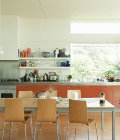 The orange-painted MDF cabinets add a pop of color to the sun-washed kitchen.  Photo by Matthew Williams.