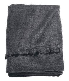 Antracietgrijs. Een geweven plaid van zachte kwaliteit met franje aan de korte zijden.