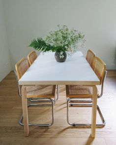 Scandinavian minimalist dining room with Cesca chairs, Artek table and wild flower bouquet.