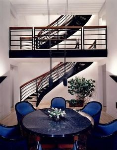 Modern Wheeler Kearns mansion dining room has high ceilings, circular dining table, electric blue chairs, hanging light fixtures, exposed walkway with metal structure and stacked curving staircases.