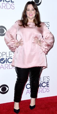 Melissa McCarthy in a pink top and black pants.
