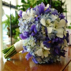 This Bridal Hand Tied Bouquet consists of Blue Hydrangeas, White Dendrobium Orchids and stunning Blue Iris.