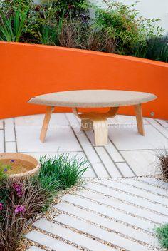 Modern patio design, wooden garden bench, with bold color orange raised bed wall, perennials, circular pattern