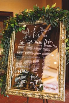 elegant seating chart features hand calligraphy in white ink on a gold framed mirror, dressed with a garland of seeded eucalyptus and lemon leaf greenery.