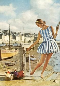 Model rinses here feet in a deckchair-striped short puffball dress on the beach from Vogue, 1960