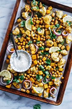 Sheet Pan Chickpea Tikka- roasted cauliflower, potatoes and chickpeas are tossed with Indian spices and served with a cooling ginger-garlic and lemon yogurt sauce. Simple to make and clean-up is a breeze! (vegan,gluten-free, grain-free)