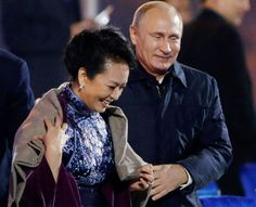 Russia's President Vladimir Putin, right, puts a shawl on Peng Liyuan, left, wife of Chinese Preside... - APEC